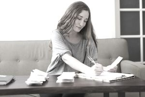 A woman is sitting on a couch and reviewing paperwork.