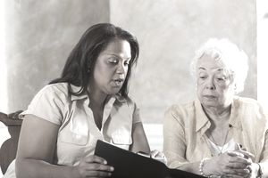 Mature Hispanic woman (50s) advising senior Hispanic woman (70s)