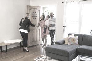 Real estate agent greeting parents with a young child at the door of a house for sale