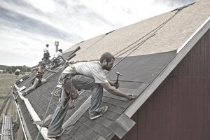 A team of workers installing a new roof on a building