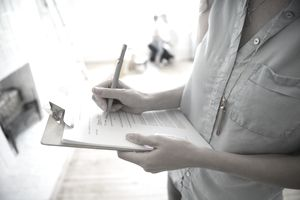 Close up woman writing on clipboard list in new house