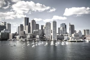 downtown Boston cityscape with sail boats afloat in the harbor