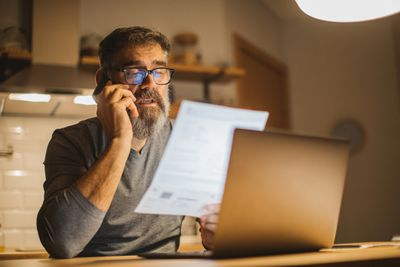 Man on phone with paperwork in front of laptop
