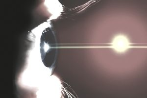 An illustration of an eye and a laser beam against a bright red background