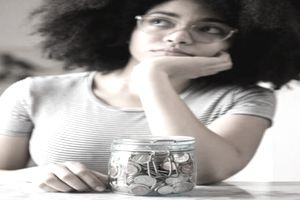 African American woman in her 20s looking anxious about her financial future with a jar of coins in front of her on table