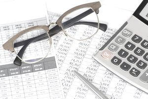 Stack of paperwork and calculator for calculating the gross profit margin of a business.
