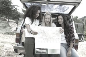 Three women sitting on the back of an open hatchback looking at map while on a road trip.
