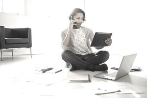 a woman speaks on a cell phone while looking at a tablet with papers, notebooks, and a laptop sitting on the floor around her