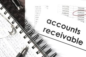 Open book with figures and paper with words accounts receivable.
