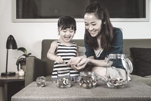Mom and child putting coins into glass jars