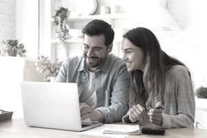 Couple sitting in front of laptop in their kitchen.