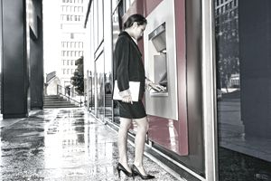 mixed race business woman outdoor ATM in city