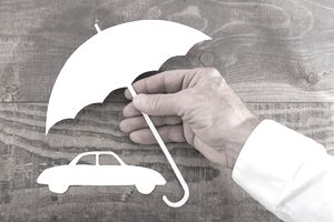Car insurance concept with a man holding an umbrella over a car