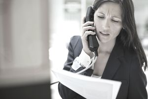 Woman on phone call holding papers