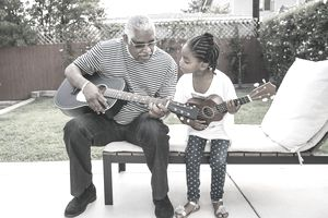 Older man teaching child to play guitar as a summer activity