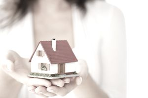 Hands holding a small model house