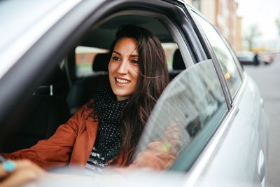 Young woman driving a sedan with a smile on her face.