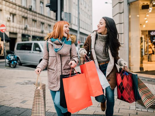 Girls laughing and carrying shopping bags coming out of a store after a shopping spree