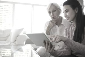 Young Woman and Grandman look at Home Insurance Coverage for heft of Cash on Tablet
