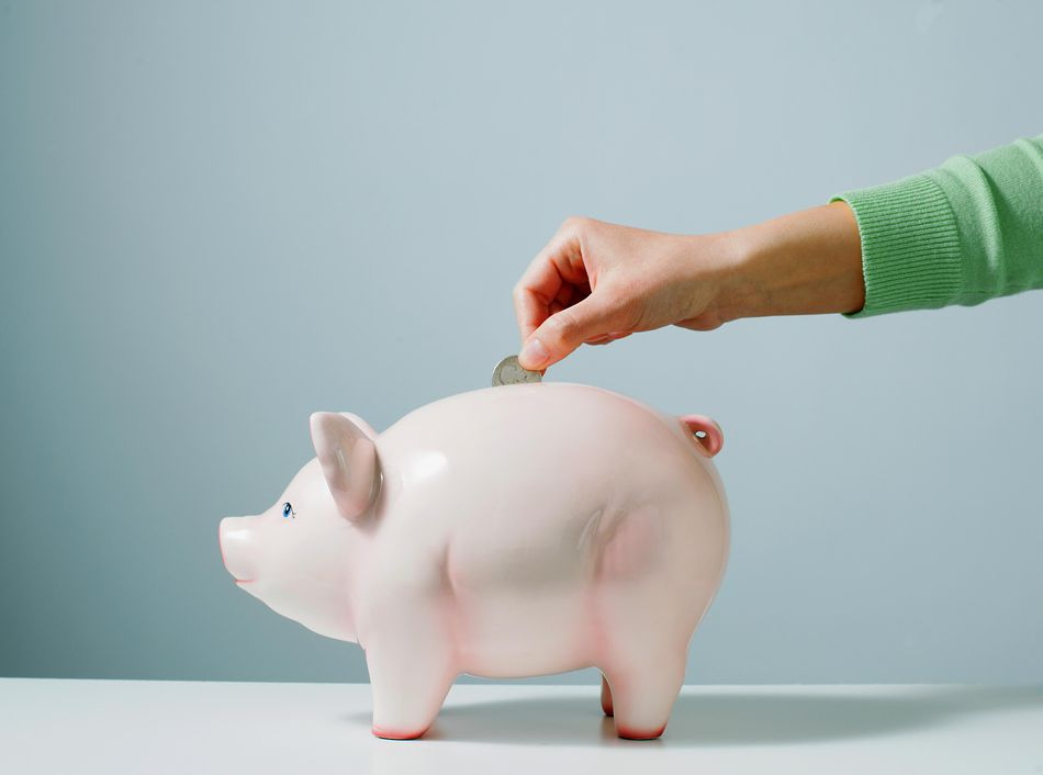 Hand placing coin in piggy bank