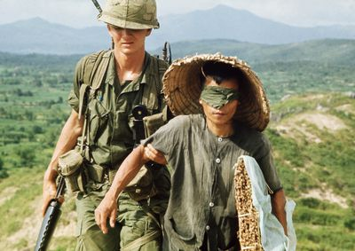 U.S. 1st Cavalry soldier escorts blindfolded Vietcong suspect during Operation Irving, 10/3.