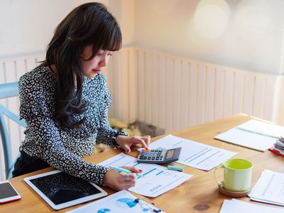 Woman at a table doing paperwork with a calculator and tablet