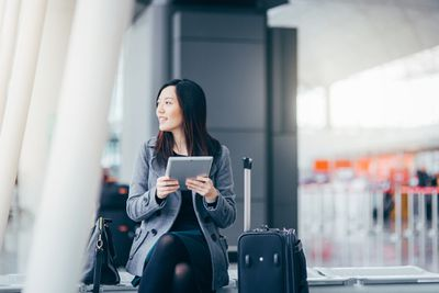 A woman waits for a flight she booked with her Amex Membership Rewards points.