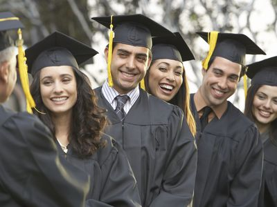 Graduate students standing in a row, outdoors - stock photo