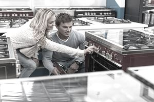 Couple admiring the big purchase of a top-of-the-line range in an appliance store