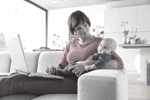 Mother and baby boy reclining on sofa with laptop