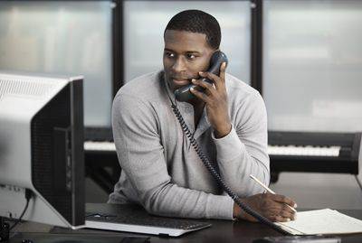 A person looking at a desktop computer while on the phone