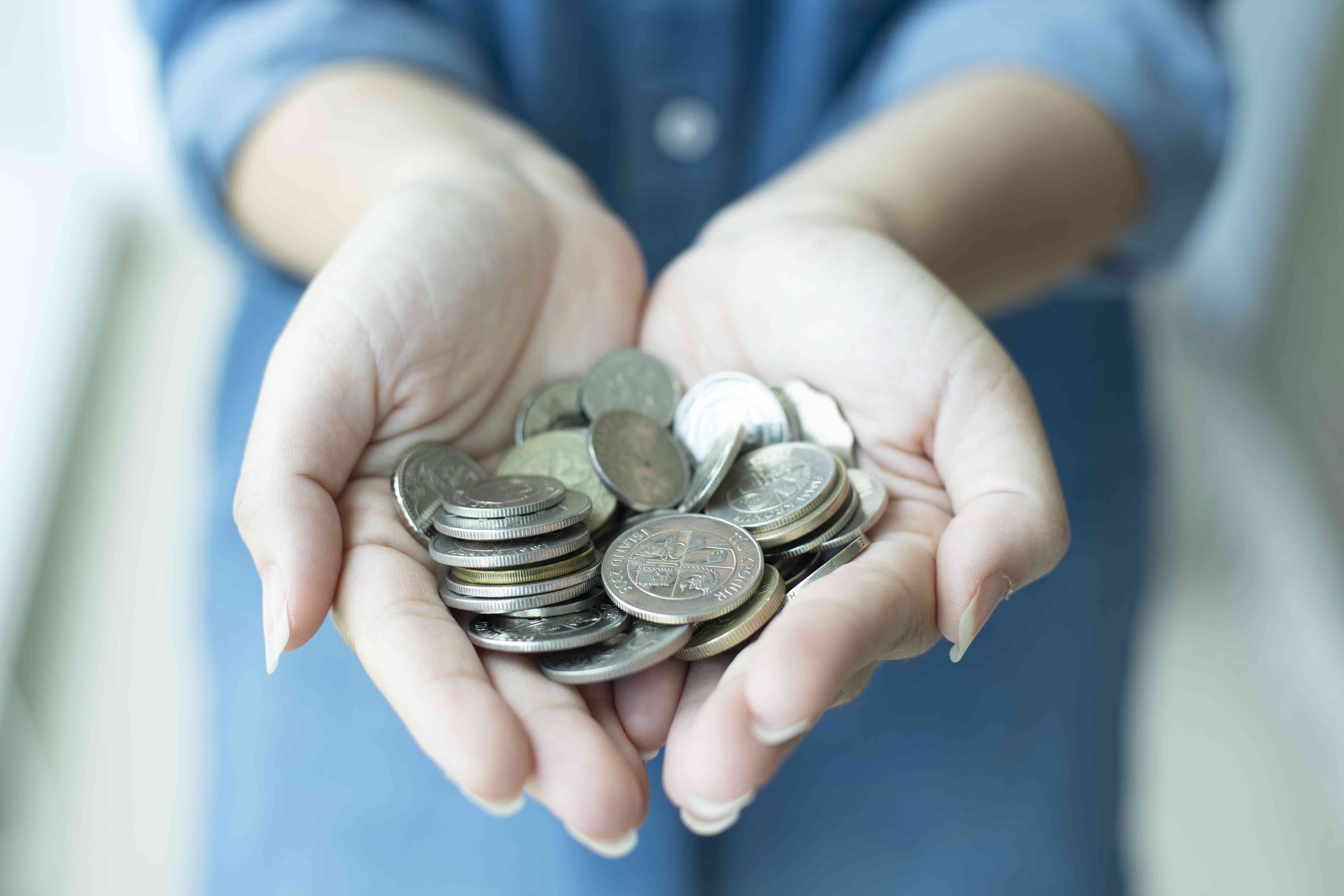 Woman with cupped hands holding coins
