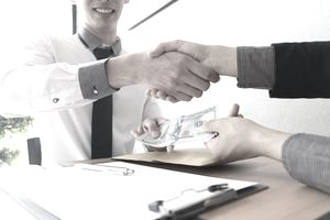 Man at Desk Shaking Hands With a Disembodied Man While Passing Him a $110 Bill