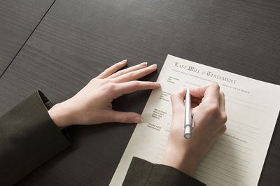 A picture of a person writing a last will and testament