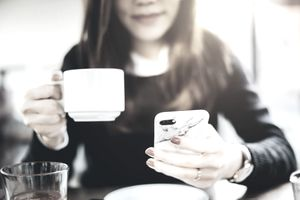 Woman holds iphone and cup of coffee