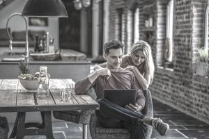 A couple looking at a laptop together in an old, rustic kitchen