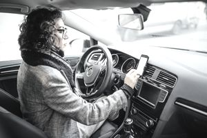 A woman sits in her car and looks at her phone, which is mounted on the air vent to track her driving using telematics
