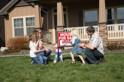 Parents and three young children placing a sold sign in front of their home