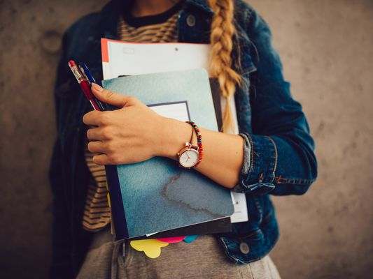 A young woman clutches textbooks, pens, and binders of papers to her torso.