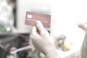 Close up of woman holding credit card with shopping list in supermarket