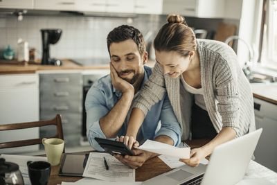 Couple in kitchen with a computer working on strategies to save money