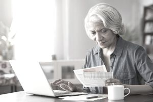 Older woman at a kitchen table looking at paper work and entering into information into laptop