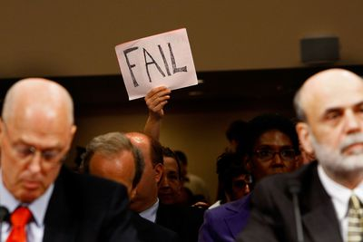 A demonstrator holds up a sign behind U.S. Treasury Secretary Henry Paulson (L) and Federal Reserve Board Chairman Ben Bernanke (R) during a hearing before the Senate Banking, Housing and Urban Affairs Committee