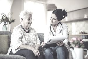 Woman and nurse on the couch, going over paperwork