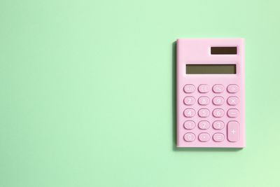 Bird's-eye view of a pink calculator on a mint green background