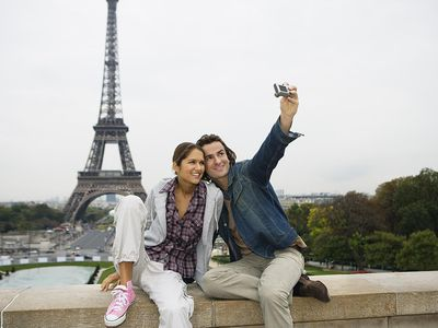 Couple sitting on wall, man taking photo, Eiffel tower in background