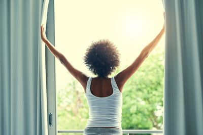 A woman opening energy efficient window curtains