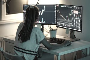 Woman consults two computer monitors with stock graphs