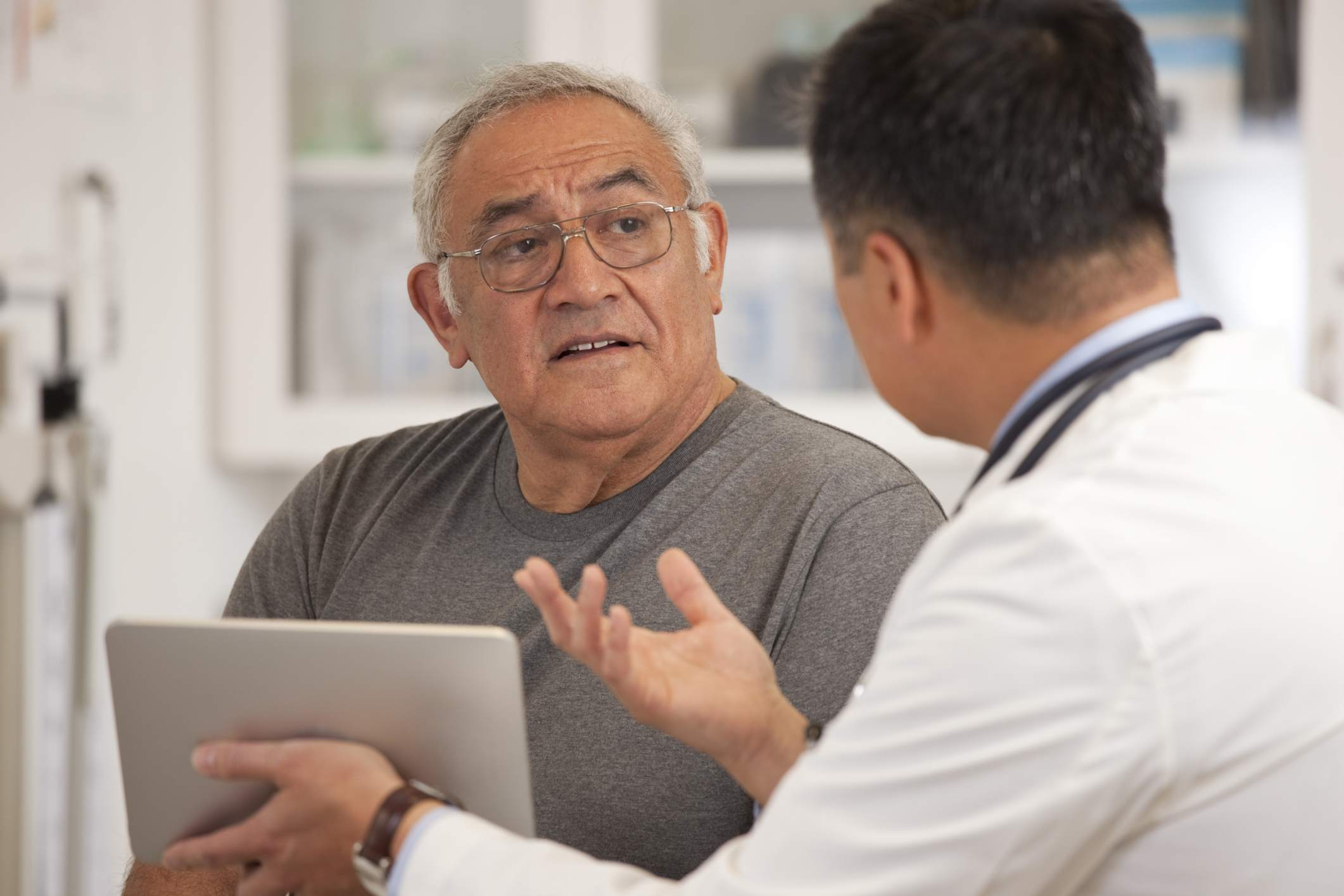 An older man talking to a doctor