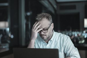 Man frustrated upset hacked using online computer for work or banking personal finances and identity theft - stock photo